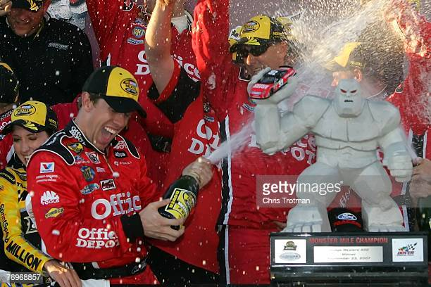 Carl Edwards driver of the Office Depot Ford celebrates with his crew members in victory lane after winning the NASCAR Nextel Cup Series Dodge...
