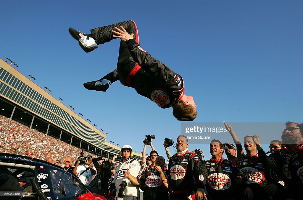 Carl Edwards, driver of the #99 Roush Racing Ford, performs a backflip as crew members look on after winning the NASCAR Nextel Cup Series Bass Pro Shops MBNA 500 on October 30, 2005 at Atlanta Motor Speedway in Hampton, Georgia.