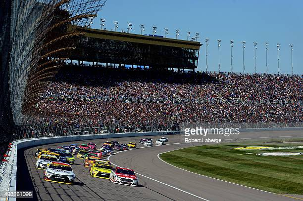 Carl Edwards driver of the Sport Clips Toyota and Kevin Harvick driver of the Budweiser/Jimmy John's Chevrolet lead the field in a restart during the...