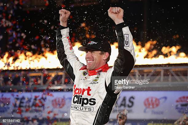 Carl Edwards driver of the Sport Clips Toyota celebrates in Victory Lane after winning the rainshortened NASCAR Sprint Cup Series AAA Texas 500 at...