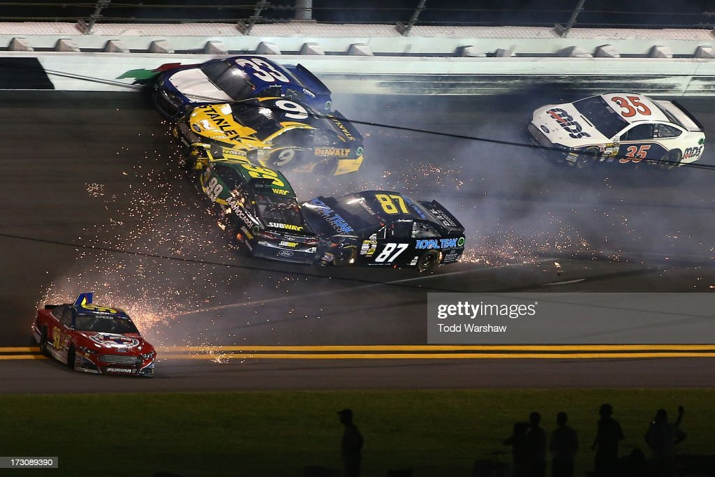 <a gi-track='captionPersonalityLinkClicked' href=/galleries/search?phrase=Carl+Edwards&family=editorial&specificpeople=193803 ng-click='$event.stopPropagation()'>Carl Edwards</a>, driver of the #99 SUBWAY Ford, <a gi-track='captionPersonalityLinkClicked' href=/galleries/search?phrase=Scott+Speed&family=editorial&specificpeople=224869 ng-click='$event.stopPropagation()'>Scott Speed</a>, driver of the #95 Leavine Family Racing Ford, <a gi-track='captionPersonalityLinkClicked' href=/galleries/search?phrase=Marcos+Ambrose&family=editorial&specificpeople=179434 ng-click='$event.stopPropagation()'>Marcos Ambrose</a>, driver of the #9 Stanley Ford, and <a gi-track='captionPersonalityLinkClicked' href=/galleries/search?phrase=Joe+Nemechek&family=editorial&specificpeople=176518 ng-click='$event.stopPropagation()'>Joe Nemechek</a>, driver of the #87 Royal Teak Collection Toyota, crash during the NASCAR Sprint Cup Series Coke Zero 400 at Daytona International Speedway on July 6, 2013 in Daytona Beach, Florida.