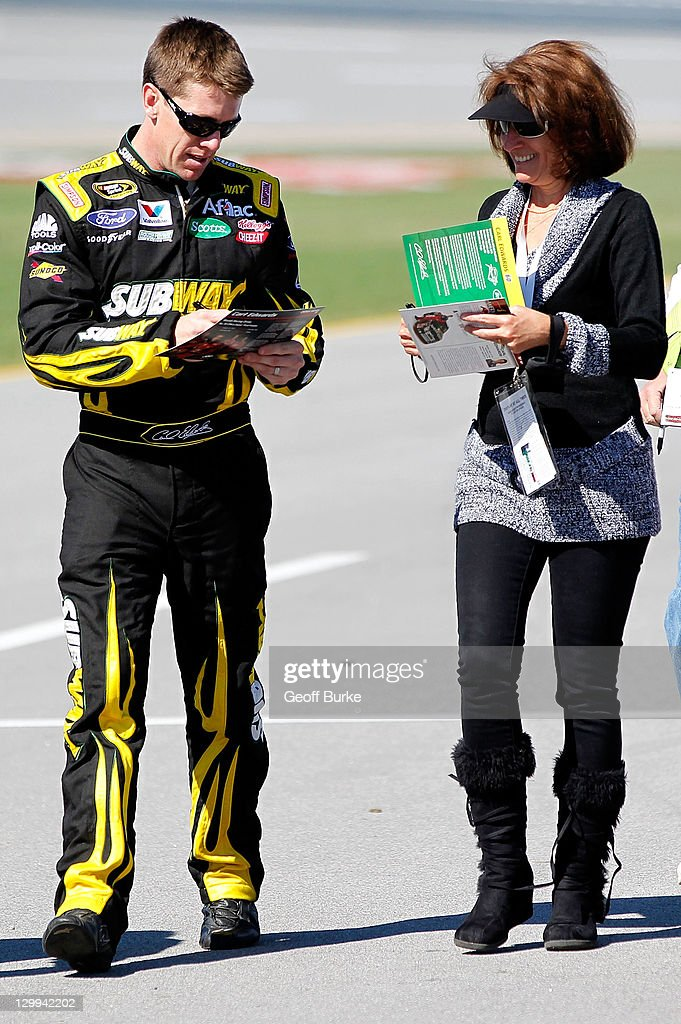 Carl Edwards driver of the Subway Ford signs an autograph during qualifying for the NASCAR Sprint Cup Series Good Sam Club 500 at Talladega...