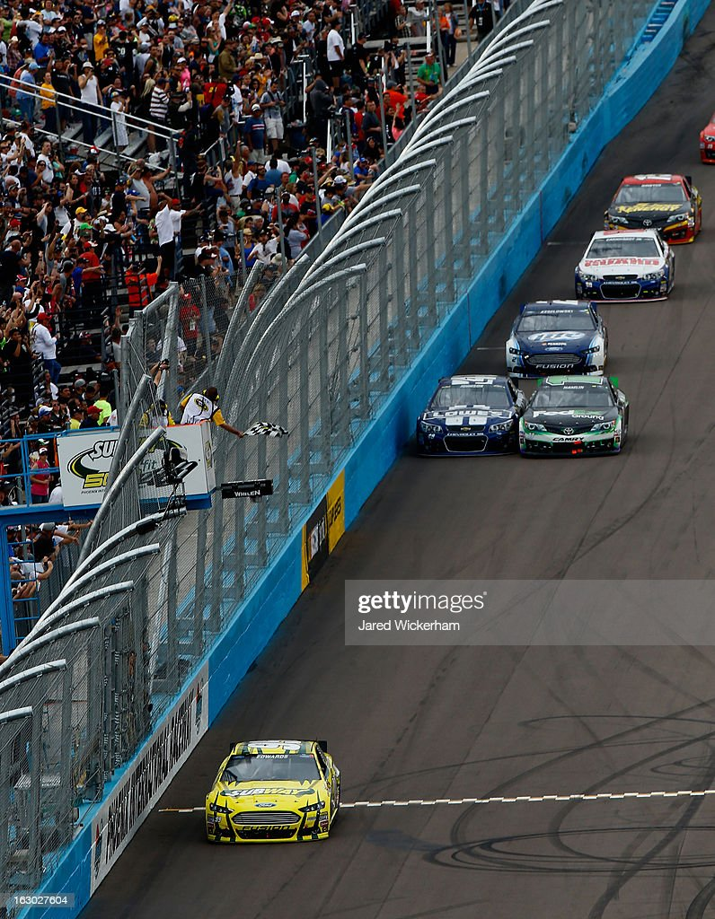 Carl Edwards driver of the Subway Ford takes the checkered flag to win the NASCAR Sprint Cup Series Subway Fresh Fit 500 at Phoenix International...