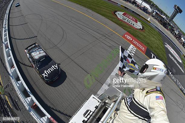 Carl Edwards driver of the XFINITY Toyota takes the checkered flag to win the NASCAR Sprint Cup Series TOYOTA OWNERS 400 at Richmond International...