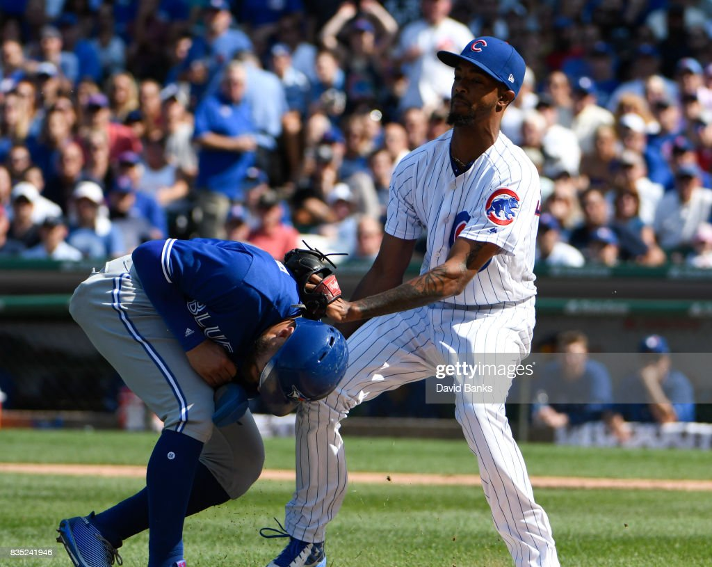 Carl Edwards Jr. (R) of the Chicago Cubs tags out Kevin Pillar #11 of the Toronto Blue Jays during the eleventh inningnon August 18, 2017 at Wrigley Field in Chicago, Illinois.
