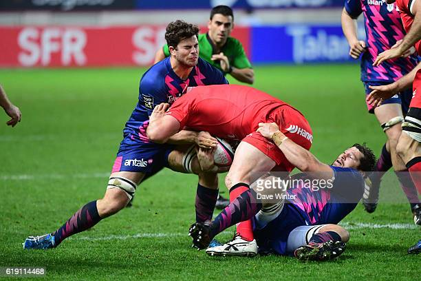 Carl Fearns of Lyon is stopped by Jonathon Ross of Stade Francais Paris and Paul Gabrillagues of Stade Francais Paris during the French Top 14...