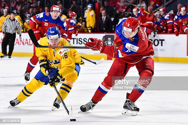 Carl Grundstrom of Team Sweden tries to poke the puck away from Kirill Urakov of Team Russia during the 2017 IIHF World Junior Championship bronze...