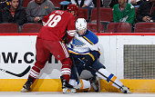 Carl Gunnarsson of the St Louis Blues battles for the puck with David Moss of the Arizona Coyotes during the NHL game at Gila River Arena on January...