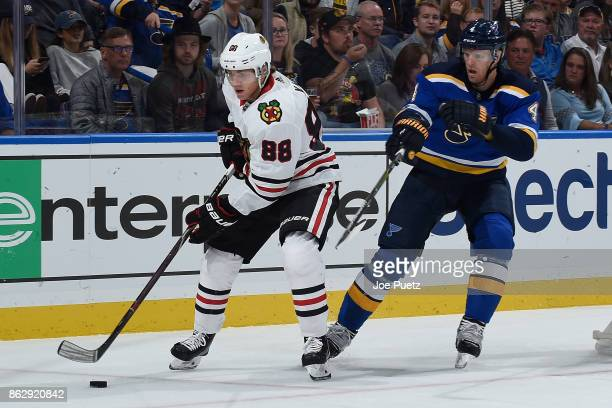 Carl Gunnarsson of the St Louis Blues defends against Patrick Kane of the Chicago Blackhawks at Scottrade Center on October 18 2017 in St Louis...