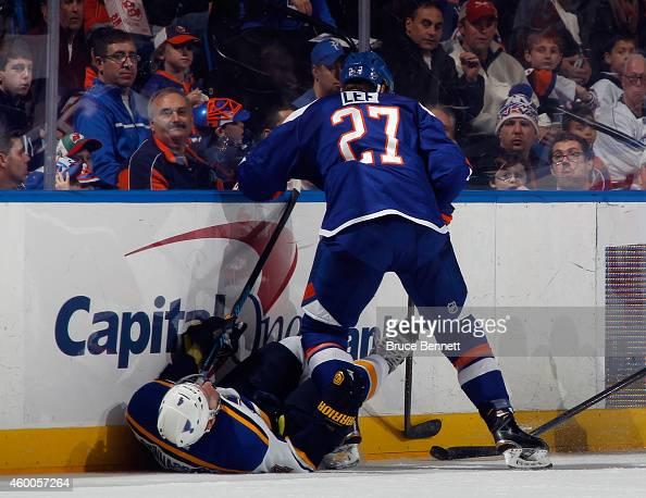 Carl Gunnarsson of the St Louis Blues is hit into the boards by Anders Lee of the New York Islanders during the second period at the Nassau Veterans...