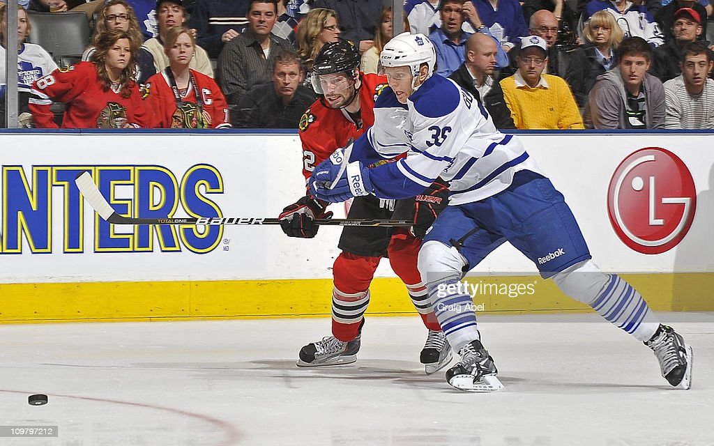 Carl Gunnarsson #36 of the Toronto Maple Leafs battles for the puck with <a gi-track='captionPersonalityLinkClicked' href=/galleries/search?phrase=Troy+Brouwer&family=editorial&specificpeople=4155305 ng-click='$event.stopPropagation()'>Troy Brouwer</a> #22 of the Chicago Blackhawks March 5, 2011 at the Air Canada Centre in Toronto, Ontario, Canada.