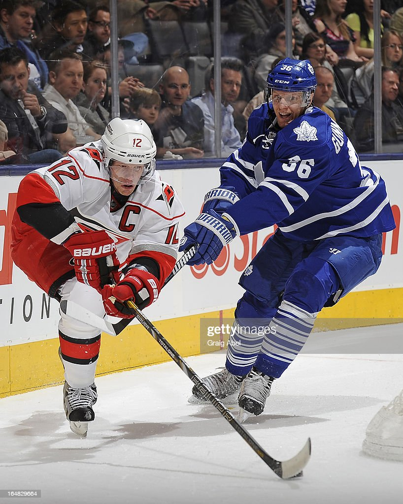 Carl Gunnarsson #36 of the Toronto Maple Leafs battles for the puck with Eric Staal #12 of the Carolina Hurricanes during NHL game action March 28, 2013 at the Air Canada Centre in Toronto, Ontario, Canada.