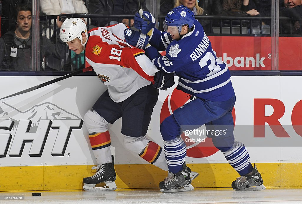 <a gi-track='captionPersonalityLinkClicked' href=/galleries/search?phrase=Carl+Gunnarsson&family=editorial&specificpeople=5557315 ng-click='$event.stopPropagation()'>Carl Gunnarsson</a> #36 of the Toronto Maple Leafs battles for the puck with Shawn Matthias #18 of the Florida Panthers during NHL game action December 17, 2013 at the Air Canada Centre in Toronto, Ontario, Canada.