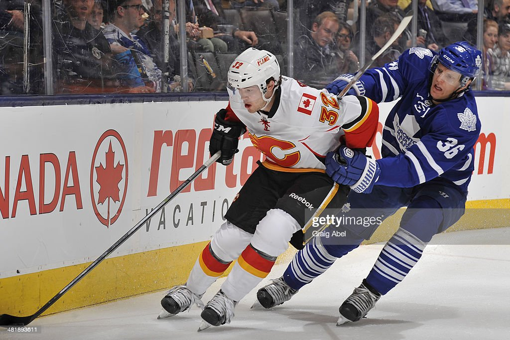 Carl Gunnarsson #36 of the Toronto Maple Leafs battles for the puck with Paul Byron #32 of the Calgary Flames during NHL game action April 1, 2014 at the Air Canada Centre in Toronto, Ontario, Canada.