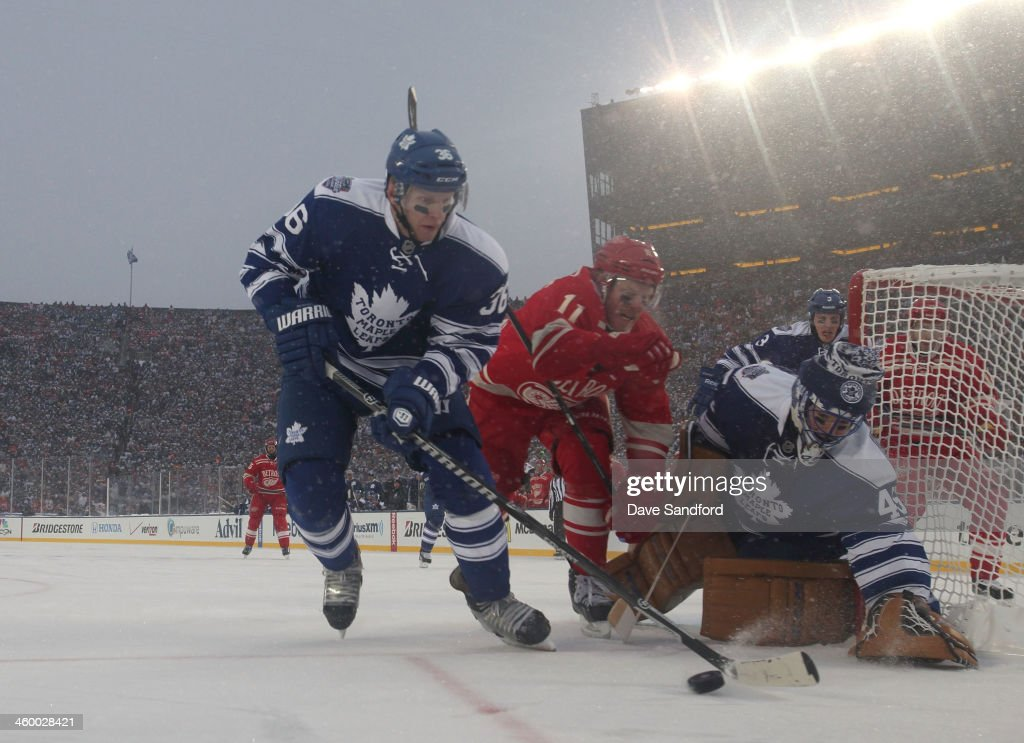 Carl Gunnarsson of the Toronto Maple Leafs controls the loose puck while under pressure from Daniel Alfredsson of the Detroit Red Wings as goaltender...