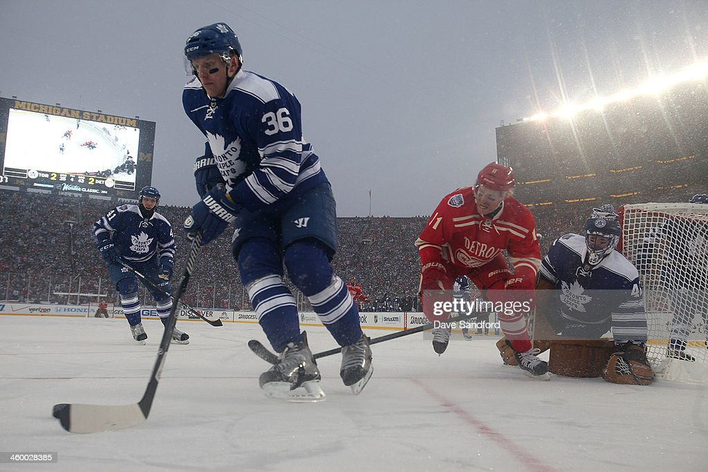 <a gi-track='captionPersonalityLinkClicked' href=/galleries/search?phrase=Carl+Gunnarsson&family=editorial&specificpeople=5557315 ng-click='$event.stopPropagation()'>Carl Gunnarsson</a> #36 of the Toronto Maple Leafs controls the puck in the defensive zone while under pressure from <a gi-track='captionPersonalityLinkClicked' href=/galleries/search?phrase=Daniel+Alfredsson&family=editorial&specificpeople=201853 ng-click='$event.stopPropagation()'>Daniel Alfredsson</a> #11 of the Detroit Red Wings as goaltender <a gi-track='captionPersonalityLinkClicked' href=/galleries/search?phrase=Jonathan+Bernier&family=editorial&specificpeople=540491 ng-click='$event.stopPropagation()'>Jonathan Bernier</a> #45 of the Toronto Maple Leafs defends his net in overtime during the 2014 Bridgestone NHL Winter Classic on January 1, 2014 at Michigan Stadium in Ann Arbor, Michigan. The Maple Leafs defeated the Red Wings 3-2 in shootout overtime.