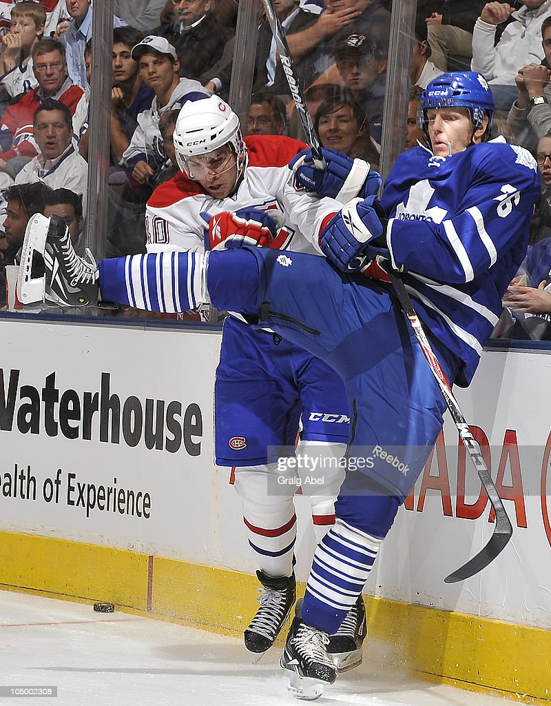 Carl Gunnarsson #36 of the Toronto Maple Leafs is checked by Maxim Lapierre #40 of the Montreal Canadiens during game action October 7, 2010 at the Air Canada Centre in Toronto, Ontario, Canada.