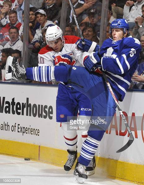 Carl Gunnarsson of the Toronto Maple Leafs is checked by Maxim Lapierre of the Montreal Canadiens during game action October 7 2010 at the Air Canada...