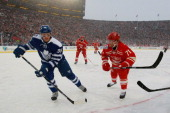Carl Gunnarsson of the Toronto Maple Leafs skates against Daniel Cleary of the Detroit Red Wings during the 2014 Bridgestone NHL Winter Classic on...