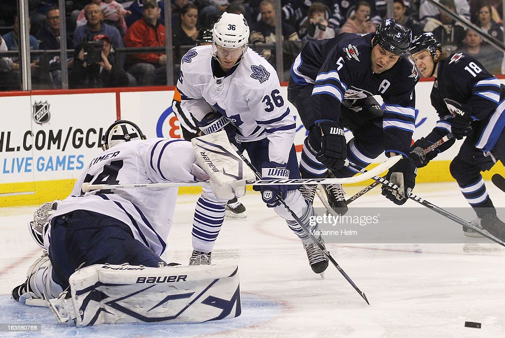 Carl Gunnarsson #36 of the Toronto Maple Leafs watches as Mark Stuart #5 of the Winnipeg Jets jumps into the air to miss the puck during a shot on goal during second period action on March 12, 2013 at the MTS Centre in Winnipeg, Manitoba, Canada.