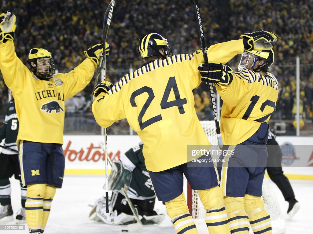 Carl Hagelin #12 of the Michigan Wolverines celebrates his third period goal with Jon Merrill #24 and Kevin Lynch #11 while playing the Michigan State Spartans at Michigan Stadium on December 11, 2010 in Ann Arbor, Michigan.