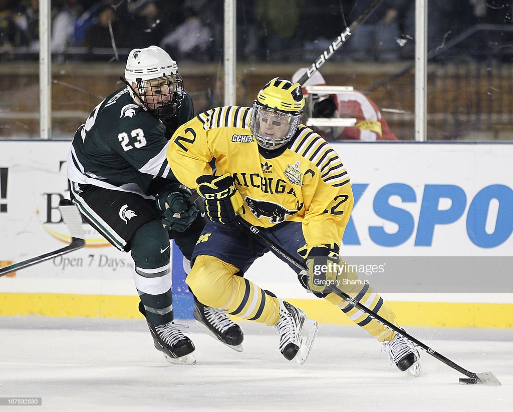 Carl Hagelin #12 of the Michigan Wolverines controls the puck in front of Luke Glendening #23 of the Michigan State Spartans at Michigan Stadium on December 11, 2010 in Ann Arbor, Michigan.