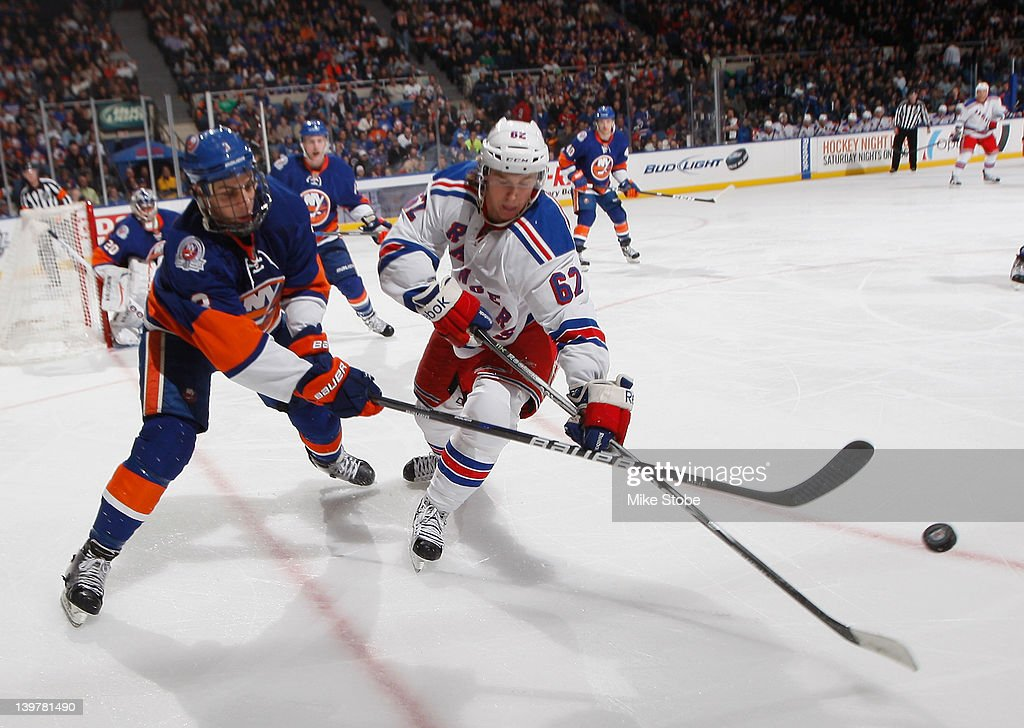 Carl Hagelin #62 of the New York Rangers and <a gi-track='captionPersonalityLinkClicked' href=/galleries/search?phrase=Travis+Hamonic&family=editorial&specificpeople=4605791 ng-click='$event.stopPropagation()'>Travis Hamonic</a> #3 of the New York Islanders lunge for the puck at Nassau Veterans Memorial Coliseum on February 24, 2012 in Uniondale, New York. The Islanders defeated the Rangers 4-3 in a shootout.