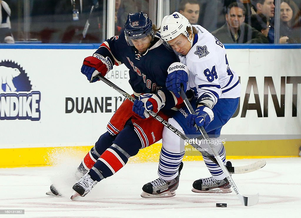 Carl Hagelin #62 of the New York Rangers battles for the puck against <a gi-track='captionPersonalityLinkClicked' href=/galleries/search?phrase=Mikhail+Grabovski&family=editorial&specificpeople=2560547 ng-click='$event.stopPropagation()'>Mikhail Grabovski</a> #84 of the Toronto Maple Leafs at Madison Square Garden on January 26, 2013 in New York City.