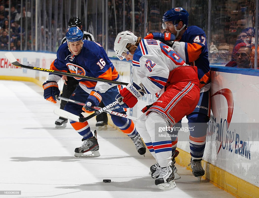 Carl Hagelin of the New York Rangers battles for the puck with Andrew MacDonald of the New York Islanders as Marty Reasoner of the New York Islanders...