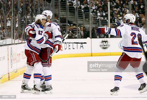 Carl Hagelin of the New York Rangers celebrates with Dominic Moore and Dan Girardi after Hagelin scores a goal in the first period against the Los...