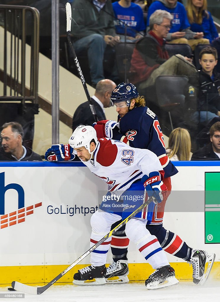 Carl Hagelin of the New York Rangers fights for the puck with Mike Weaver of the Montreal Canadiens in the second period at Madison Square Garden on...