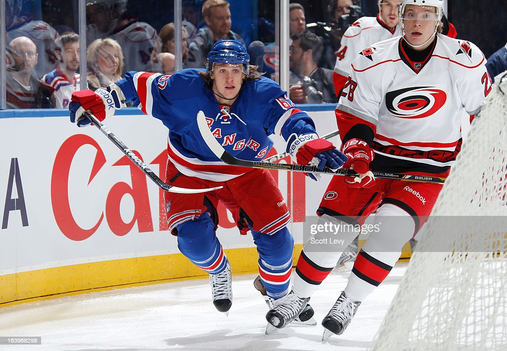 Carl Hagelin #62 of the New York Rangers skates past Alexander Semin #28 of the Carolina Hurricanes behind the net at Madison Square Garden on March 18, 2013 in New York City.