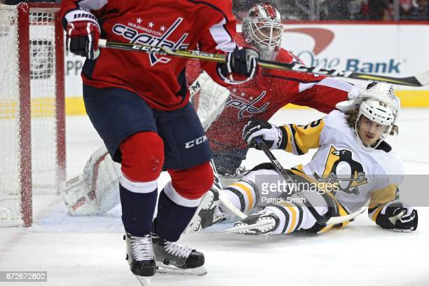 Carl Hagelin of the Pittsburgh Penguins collides with goalie Braden Holtby of the Washington Capitals during the first period at Capital One Arena on...