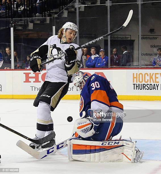 Carl Hagelin of the Pittsburgh Penguins screens JeanFrancois Berube of the New York Islanders during the first period at the Barclays Center on April...