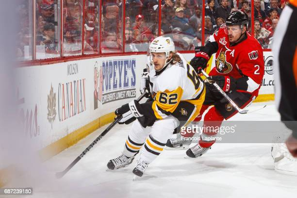 Carl Hagelin of the Pittsburgh Penguins skates with the puck against Dion Phaneuf of the Ottawa Senators in Game Four of the Eastern Conference Final...