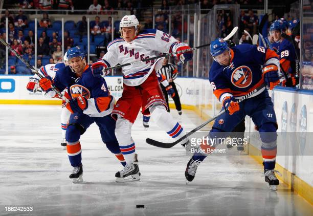 Carl Hagelin skates against Radek Martinek and Thomas Vanek of the New York Islanders during the first period at the Nassau Veterans Memorial...