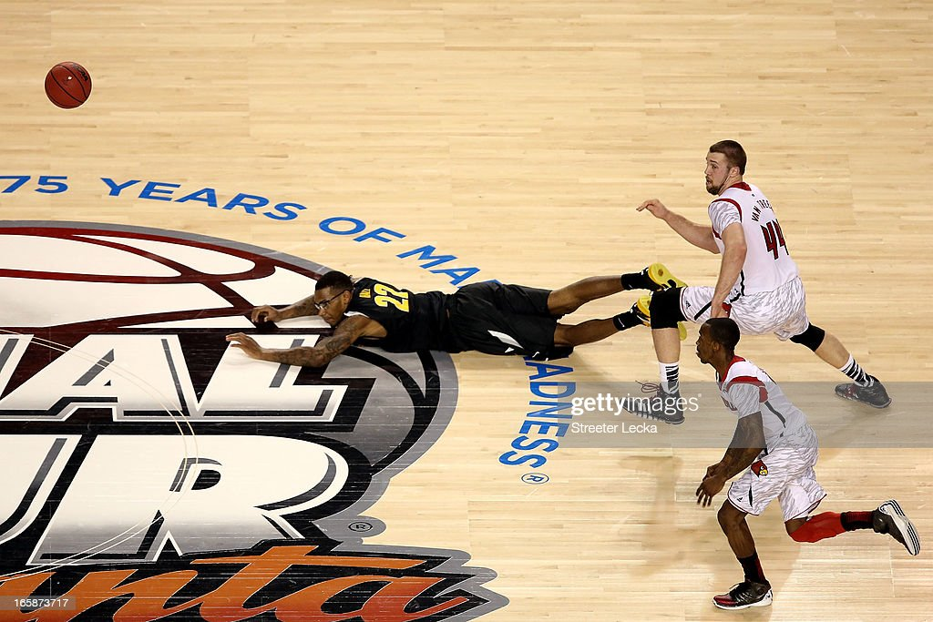 Carl Hall #22 of the Wichita State Shockers dives for a loose ball in front of Stephan Van Treese #44 and Peyton Siva #3 of the Louisville Cardinals in the second half during the 2013 NCAA Men's Final Four Semifinal at the Georgia Dome on April 6, 2013 in Atlanta, Georgia.