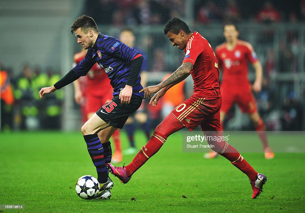 Carl Jenkinson of Arsenal is challenged by Luiz Gustavo of Bayern Muenchen during the UEFA Champions League Round of 16 second leg match between Bayern Muenchen and Arsenal at Allianz Arena on March 13, 2013 in Munich, Germany.