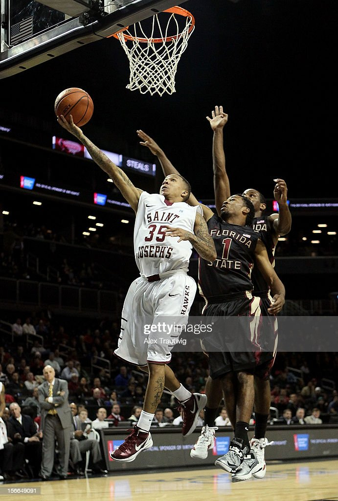 Carl Jones #35 of the Saint Joseph's Hawks goes up for a shot against Devon Bookert #1 of the Florida State Seminoles during the championship game of the Coaches Vs. Cancer Classic at the Barclays Center on November 17, 2012 in the Brooklyn borough of New York City.