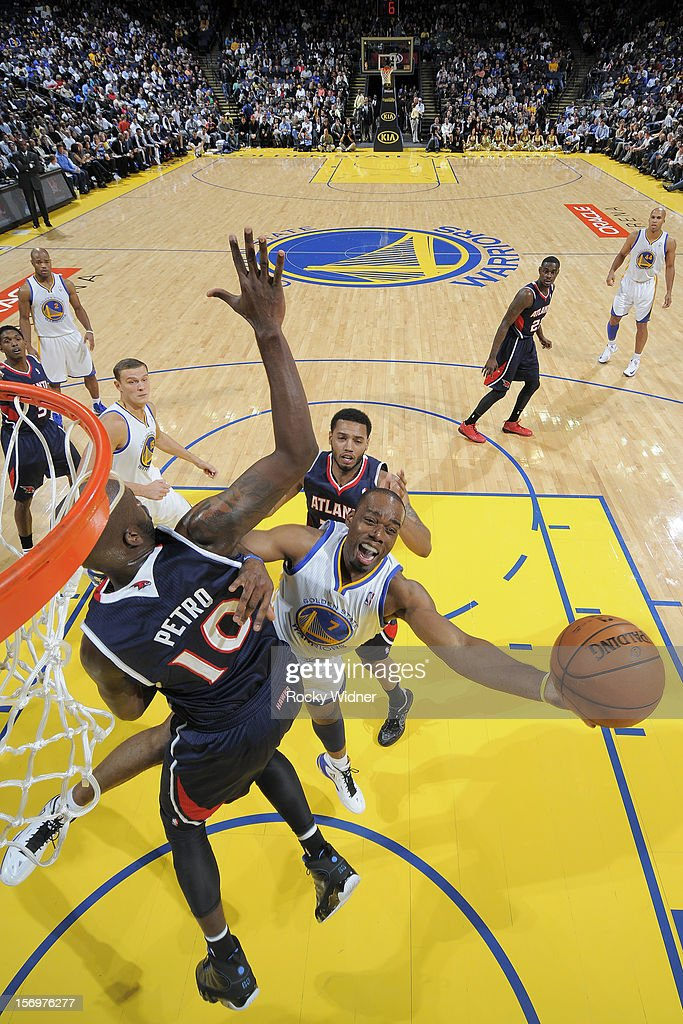 Carl Landry of the Golden State Warriors puts up a shot against Johan Petro of the Atlanta Hawks on November 14 2012 at Oracle Arena in Oakland...