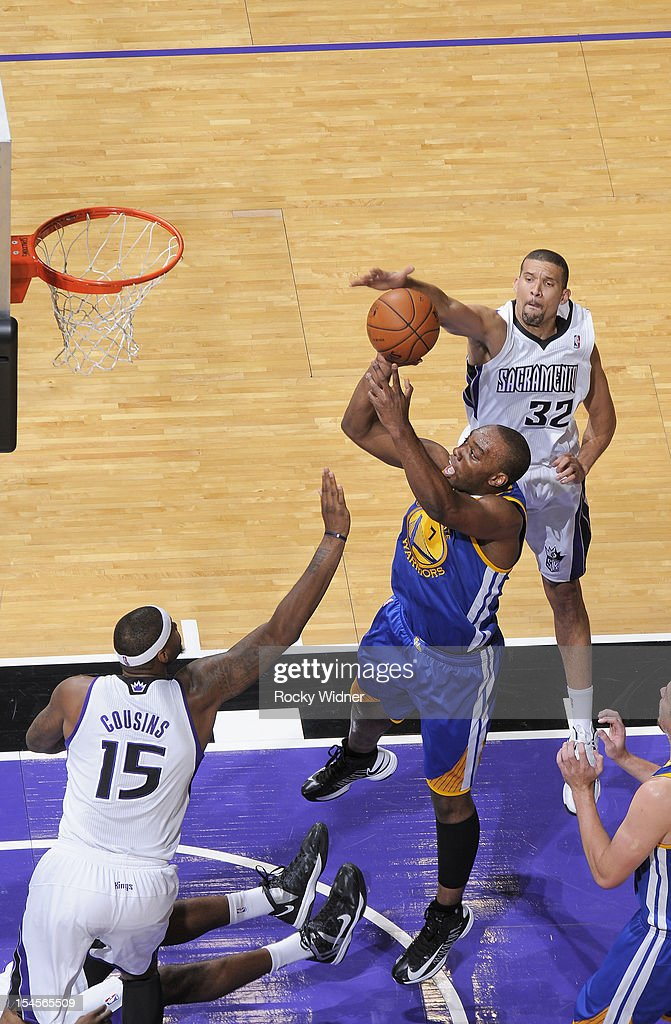 Carl Landry #7 of the Golden State Warriors puts up a shot over DeMarcus Cousins #15 and Francisco Garcia #32 of the Sacramento Kings on October 17, 2012 at Power Balance Pavilion in Sacramento, California.