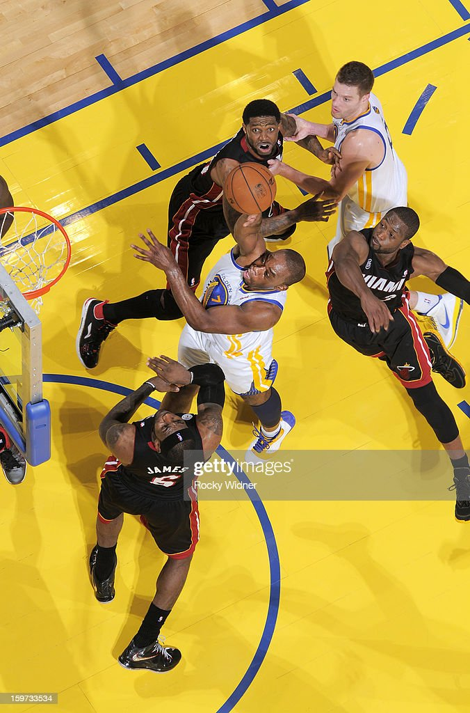 Carl Landry #7 of the Golden State Warriors shoots against LeBron James #6 and Dwyane Wade #3 of the Miami Heat on January 16, 2013 at Oracle Arena in Oakland, California.