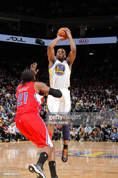 Carl Landry of the Golden State Warriors shoots against Ronny Turiaf of the Los Angeles Clippers on January 21 2013 at Oracle Arena in Oakland...