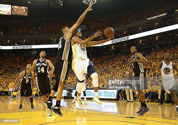 Carl Landry of the Golden State Warriors shoots against Tim Duncan of the San Antonio Spurs in Game Four of the Western Conference Semifinals during...