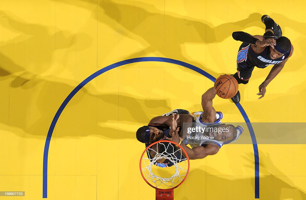 Carl Landry #7 of the Golden State Warriors shoots over Brendan Haywood #33 of the Charlotte Bobcats on December 21, 2012 at Oracle Arena in Oakland, California.