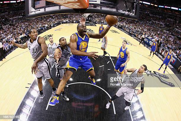 Carl Landry of the Golden State Warriors takes a shot against Tim Duncan of the San Antonio Spurs during Game Five of the Western Conference...