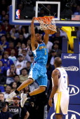 Carl Landry of the Golden State Warriors watches as Dominic McGuire of the New Orleans Hornets dunks the ball at Oracle Arena on December 18 2012 in...