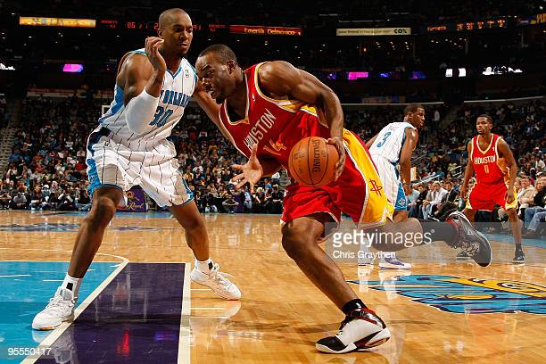 Carl Landry of the Houston Rockets drives the ball around David West of the New Orleans Hornets at the New Orleans Arena on January 2 2010 in New...