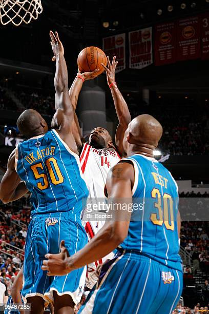 Carl Landry of the Houston Rockets shoots the ball over David West and Emeka Okafor of the New Orleans Hornets on December 29 2009 at the Toyota...