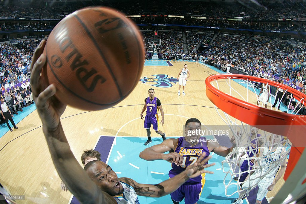 <a gi-track='captionPersonalityLinkClicked' href=/galleries/search?phrase=Carl+Landry&family=editorial&specificpeople=4111952 ng-click='$event.stopPropagation()'>Carl Landry</a> #24 of the New Orleans Hornets dunks over <a gi-track='captionPersonalityLinkClicked' href=/galleries/search?phrase=Andrew+Bynum&family=editorial&specificpeople=630695 ng-click='$event.stopPropagation()'>Andrew Bynum</a> #17 of the Los Angeles Lakers on April 9, 2012 at the New Orleans Arena in New Orleans, Louisiana.